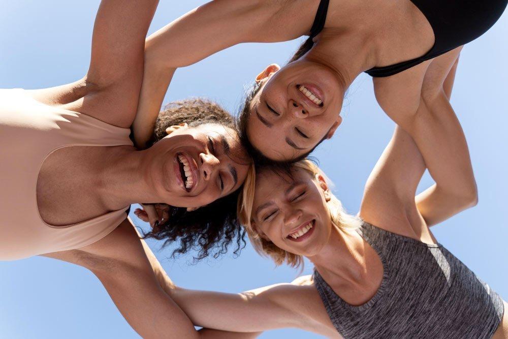 Tre ragazze che si stringono in un abbraccio guardando verso la telecamera situata in basso