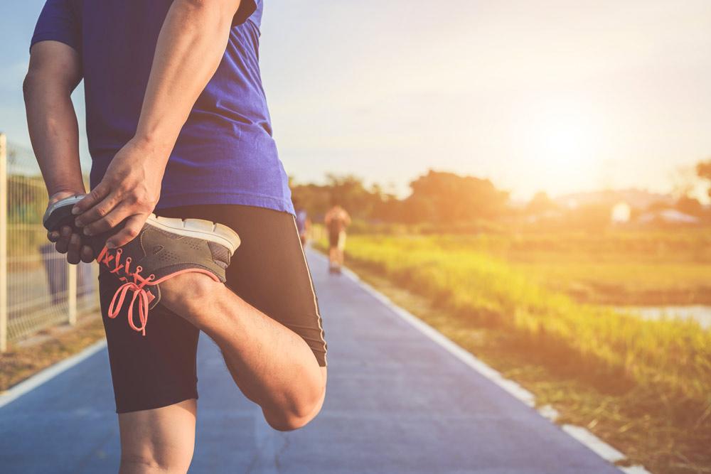 Corritore riscalda il suo corpo prima di iniziare a correre lungo il percorso.