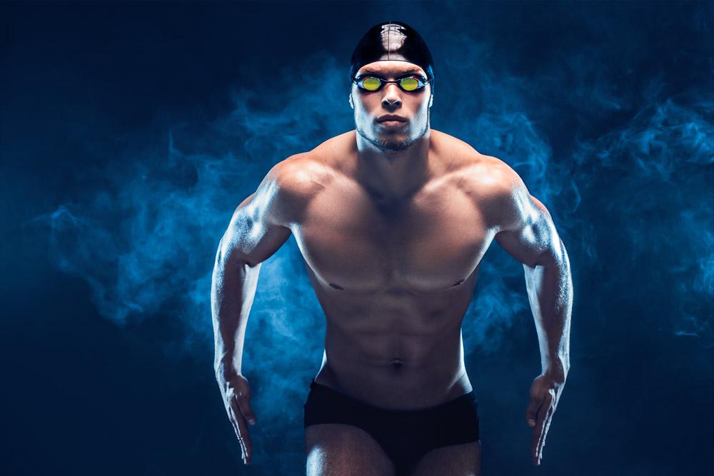 Nuotatore attraente e muscoloso pronto a tuffarsi in acqua e careggiare