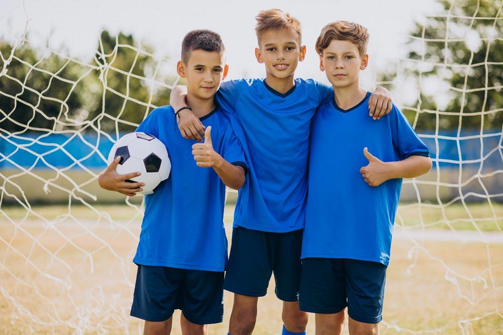 Tre bambini, giocatori di una squadra di calcio, in campo a chiusura partita.