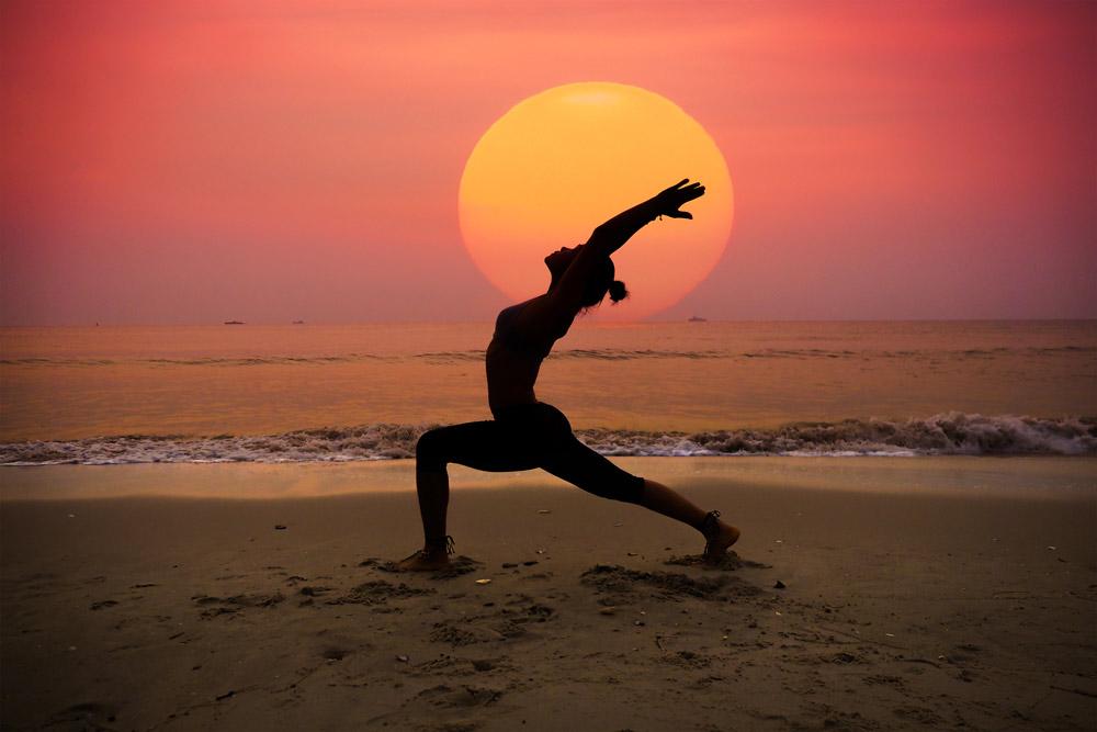 Ragazza che pratica yoga al mare con un bellissimo tramonto dietro di lei