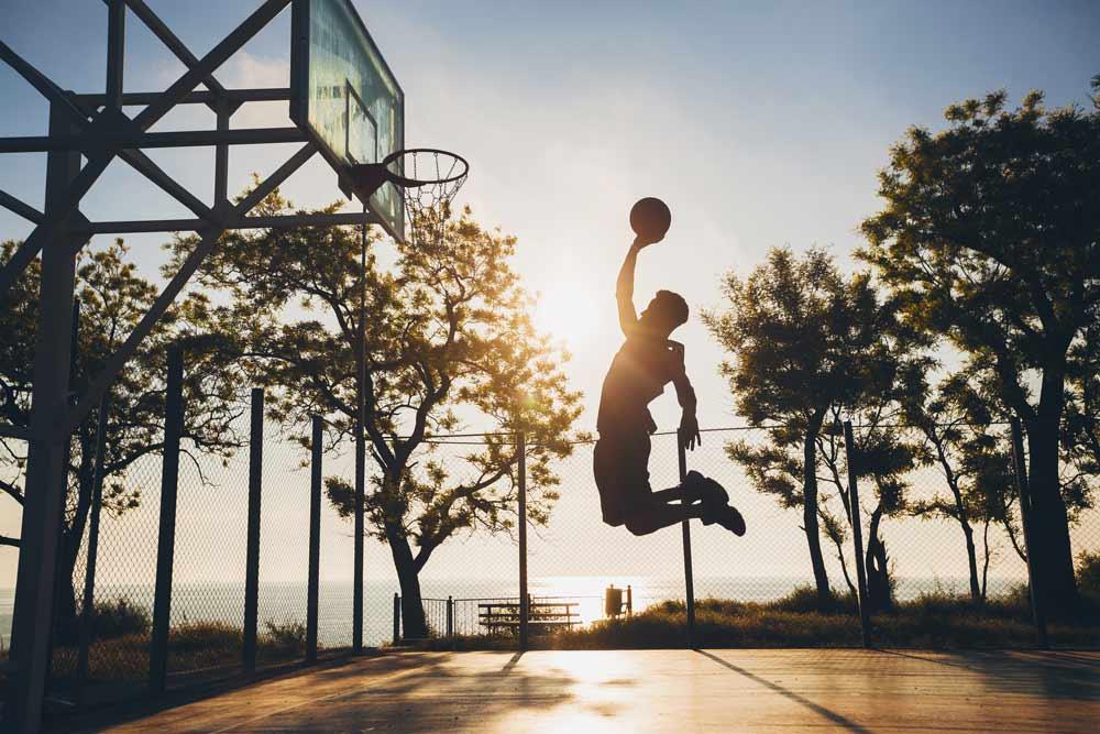 Ragazzo che gioca a basket al tramonto