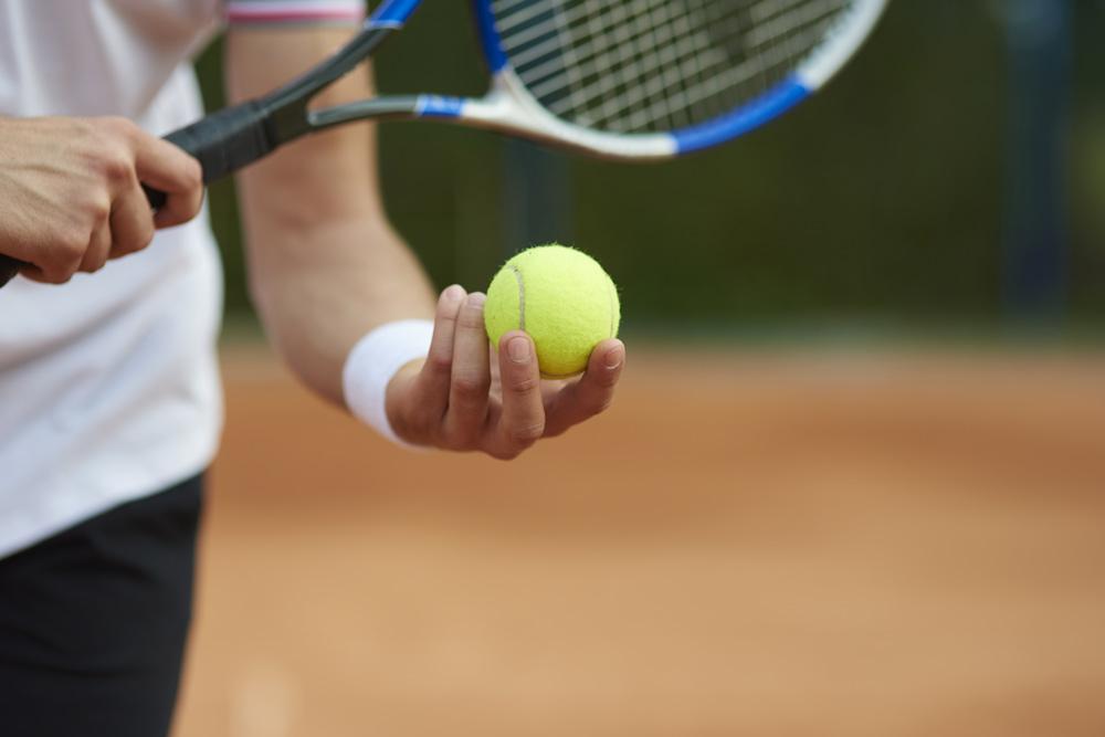 Tennista con in mano la pallina di tennis, pronto a lanciarla in alto per iniziare la partita